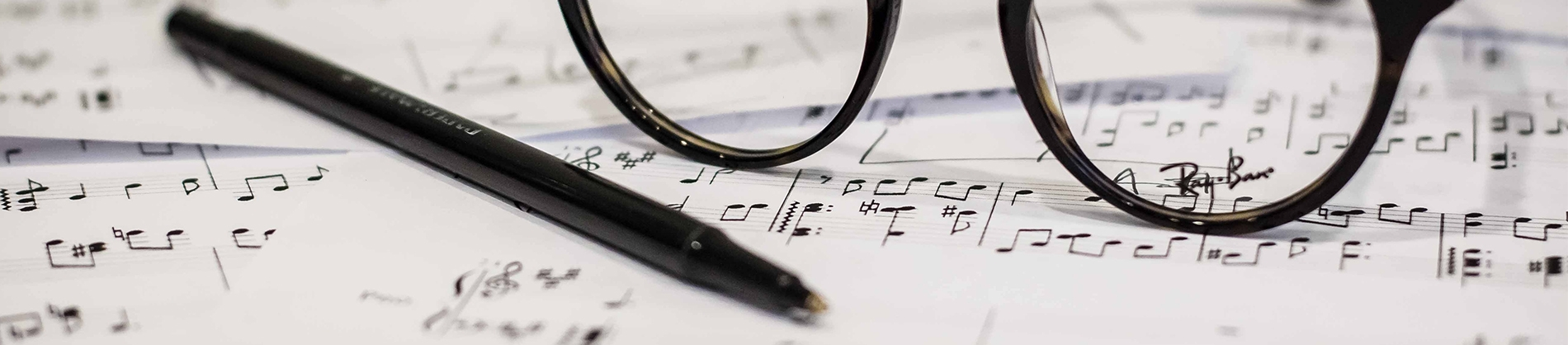 Sheet music with a pair of glasses and pen resting on top