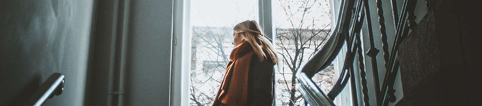 A women in a orange scarf coming down the stairs and looking out of a large window