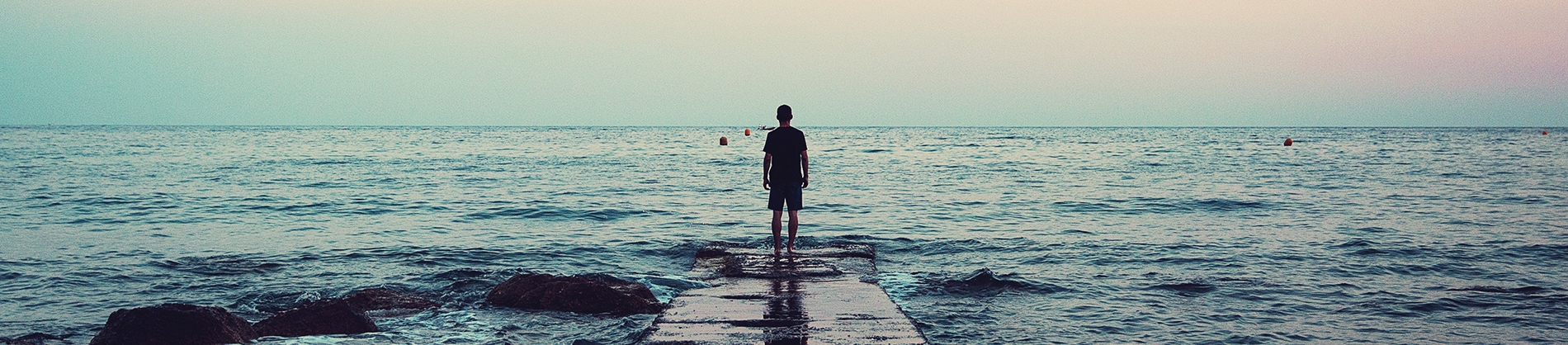 A man stood on the end of a wooden pier looking out to sea