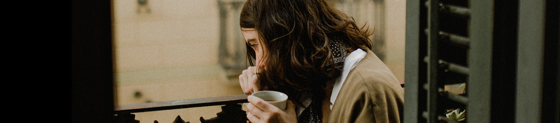 A women sat with her head resting on her hand, looking over a balcony with a mug of coffee in her hand