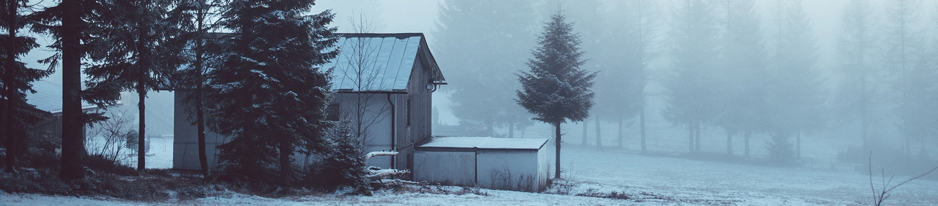 A small farm house covered in snow surrounded by forest