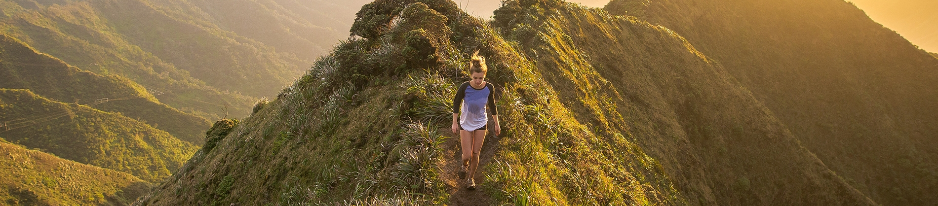 A women running down a hill with the sun rising behind her