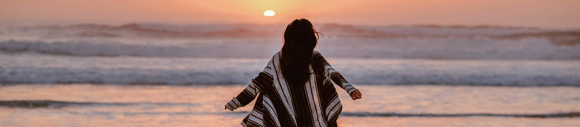 A women with her arms out beside her looking towards a sunset and the ocean
