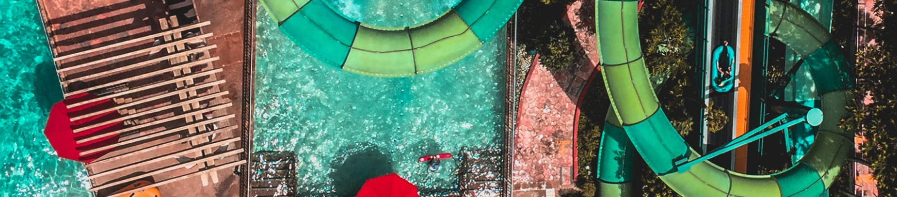 A birds-eye view of a water park with a green flume ride