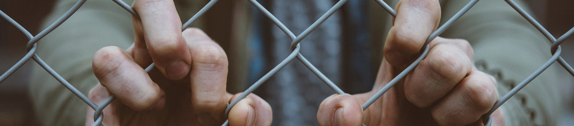 A person standing behind a wire fence holding on to the wire with their hands